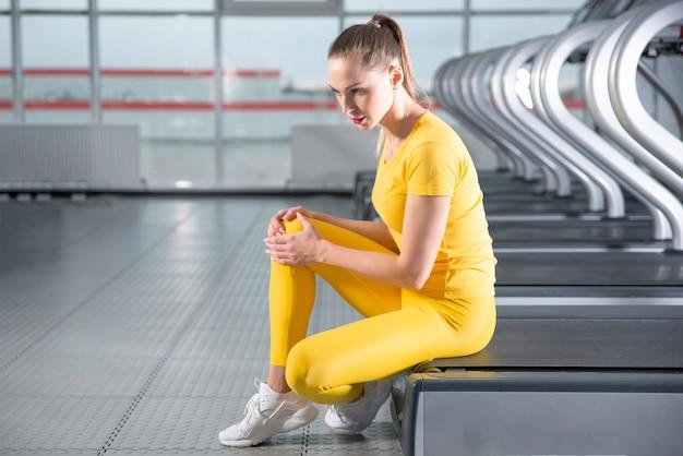 Giovane donna con un ginocchio infortunato seduto sul tapis roulant in palestra sentendo dolore dopo l'esecuzione Foto Premium