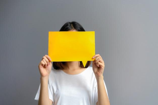 Giovane donna con un poster vuoto per il testo su uno sfondo bianco. Foto Premium