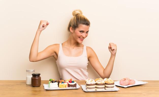Giovane donna con un sacco di diverse mini torte in un tavolo per celebrare una vittoria Foto Premium