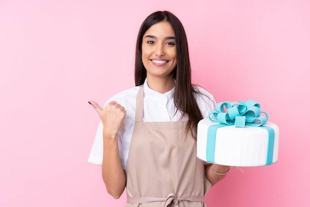 Giovane donna con una grande torta sul muro isolato che punta verso il lato per presentare un prodotto Foto Premium