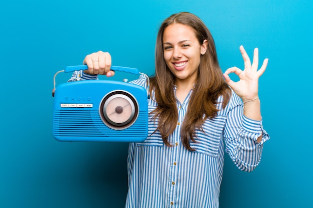 Giovane donna con una radio d'annata contro il blu Foto Premium