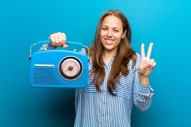 Giovane donna con una radio vintage su sfondo blu Foto Premium