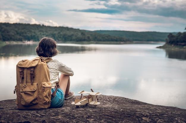 Giovane donna con zaino e aereo modello sul lago Foto Premium