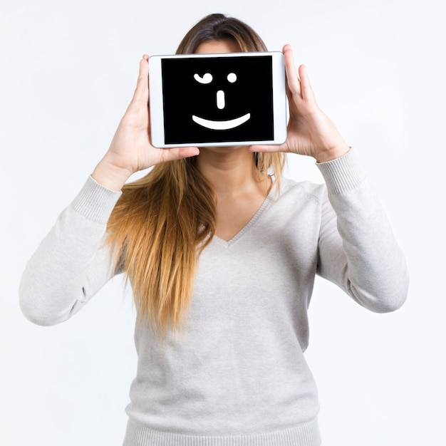 Giovane donna copre il suo volto con compressa digitale. isolato su sfondo bianco Foto Gratuite