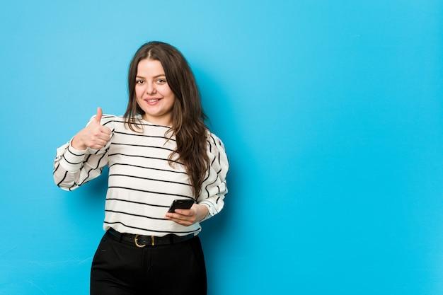 Giovane donna curvy che tiene un telefono che sorride e che alza pollice in su Foto Premium