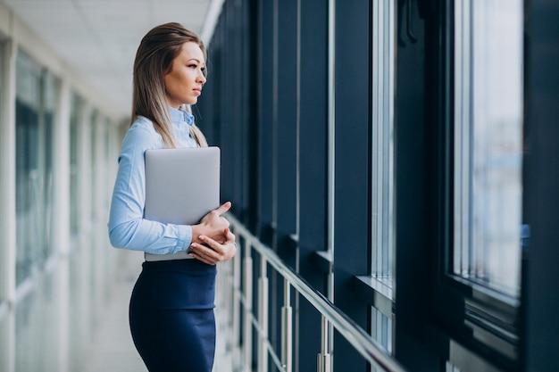 Giovane donna d'affari con il portatile in piedi in un ufficio Foto Gratuite