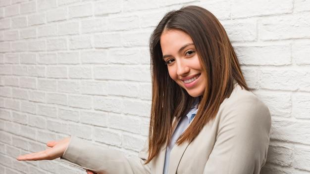Giovane donna d'affari in possesso di qualcosa con le mani Foto Premium