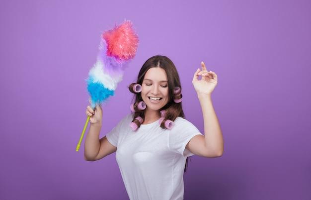 Giovane donna dai capelli castani divertirsi durante la pulizia. Foto Premium