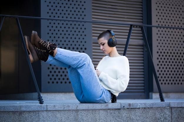 Giovane donna dai capelli corti che si siede e ascolta la musica all'aperto Foto Gratuite