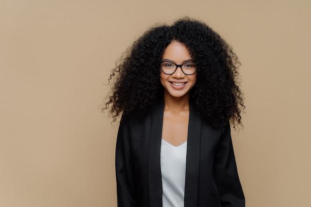 Giovane donna dai capelli ricci felice con il sorriso a trentadue denti Foto Premium