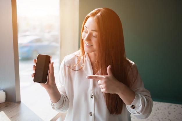 Giovane donna dai capelli rossi che si siede in un caffè e che tiene un telefono. il modello femminile punta con un dito indice sullo smartphone. Foto Premium