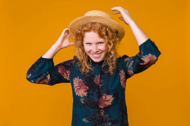 Giovane donna dai capelli rossi in cappello e vestito ...