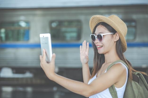 Giovane donna dei viaggiatori con lo zaino che guarda la compressa della tenuta alla stazione ferroviaria. giorno del turismo Foto Premium