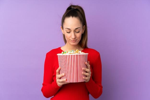 Giovane donna del brunette sopra la parete viola isolata che tiene un grande secchio di popcorn Foto Premium