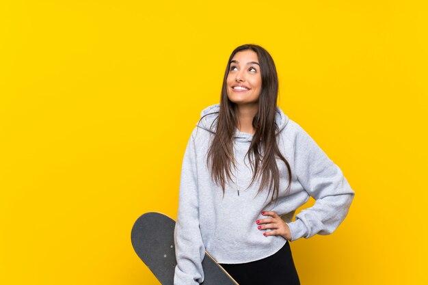 Giovane donna del pattinatore isolata sul cercare giallo mentre sorridendo Foto Premium