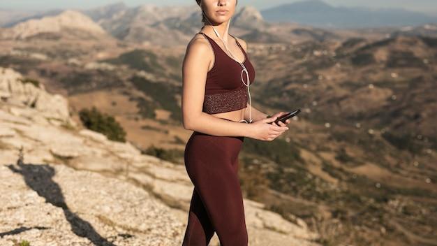Giovane donna del primo piano sull'yoga di pratica della montagna Foto Gratuite