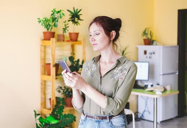 Giovane donna del ritratto che manda un sms facendo uso dello smart phone Foto Premium