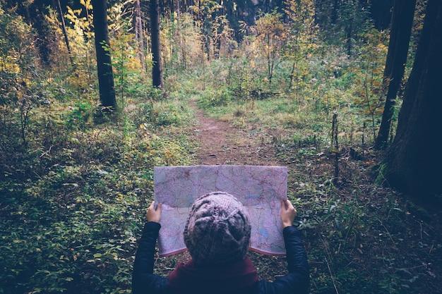 Giovane donna del viaggiatore con la mappa, alla foresta di verde di autunno nel giorno soleggiato. Foto Premium