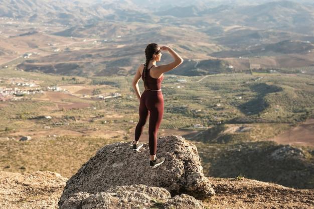 Giovane donna dell'angolo alto sul distogliere lo sguardo della montagna Foto Gratuite