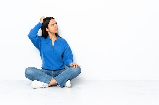 Giovane donna della corsa mista che si siede sul pavimento isolato su fondo bianco che ha dubbi mentre graffiando testa Foto Premium