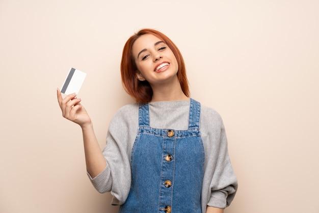 Giovane donna della testarossa sopra la parete isolata che tiene una carta di credito e un pensiero Foto Premium
