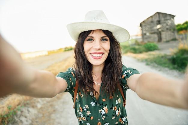 Giovane donna della viandante che prende una fotografia del selfie all'aperto Foto Premium