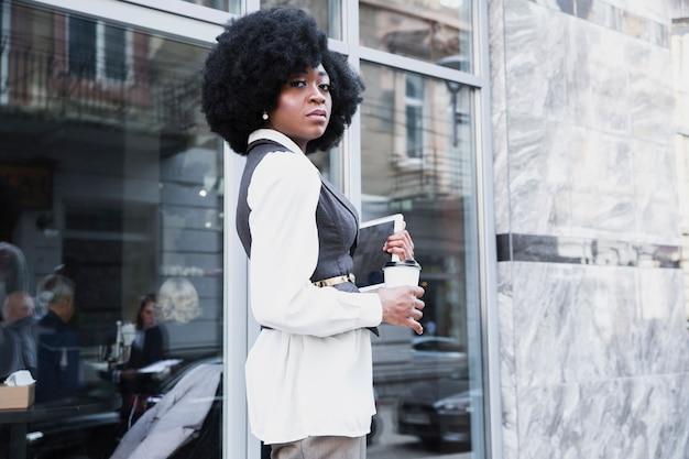 Giovane donna di affari africana sicura che sta fuori dell'ufficio che tiene compressa digitale e tazza di caffè a gettare Foto Gratuite