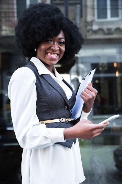 Giovane donna di affari africana sicura felice che per mezzo del telefono cellulare Foto Gratuite