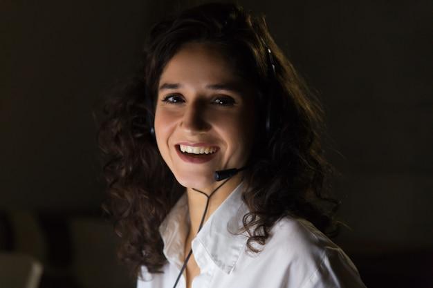 Giovane donna di affari allegra in cuffia avricolare Foto Gratuite