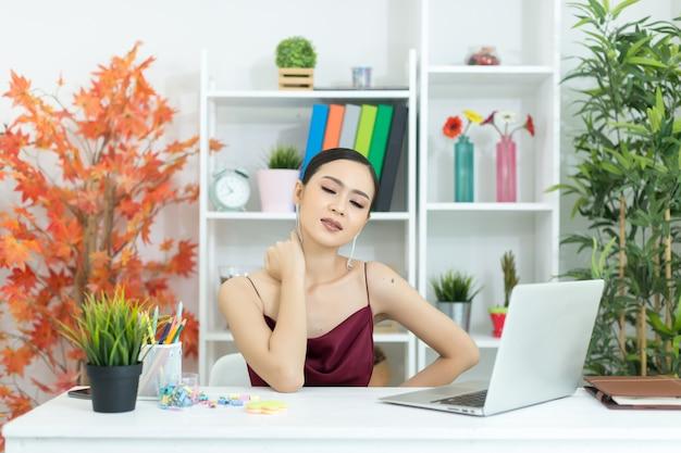 Giovane donna di affari asiatica che tocca massaggio torcicollo Foto Gratuite