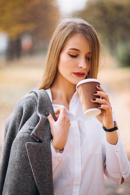 Giovane donna di affari che beve caffè all'aperto Foto Gratuite