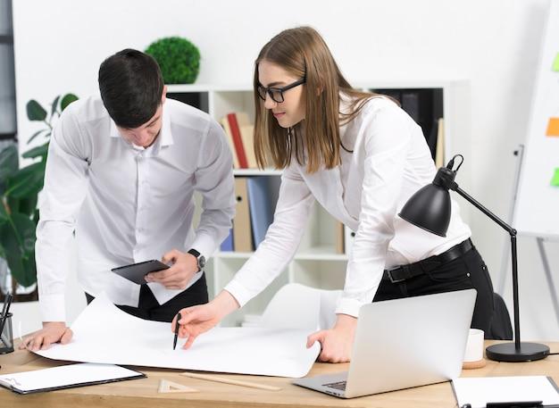 Giovane donna di affari che discute progetto con il suo collega maschio su libro bianco sopra lo scrittorio Foto Gratuite