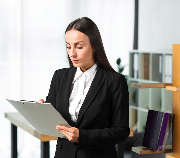 Giovane donna di affari che scrive sulla lavagna per appunti con la penna Foto Gratuite