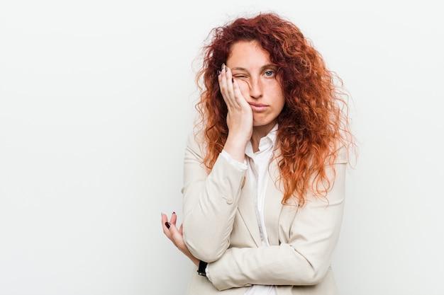 Giovane donna di affari naturale rossa su sfondo bianco che è annoiato, affaticato e ha bisogno di una giornata di relax. Foto Premium