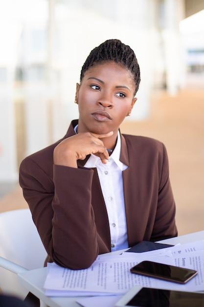 Giovane donna di affari pensierosa che pensa sopra i termini del contratto Foto Gratuite