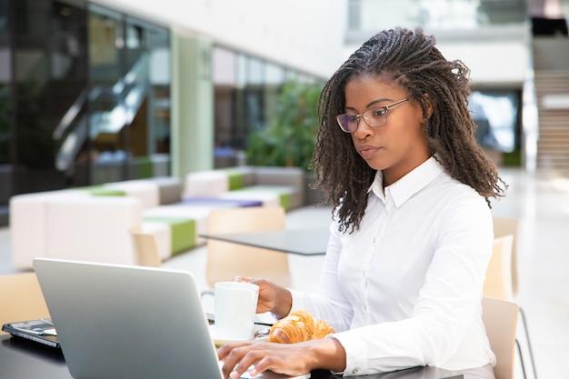 Giovane donna di affari seria che mangia prima colazione Foto Gratuite
