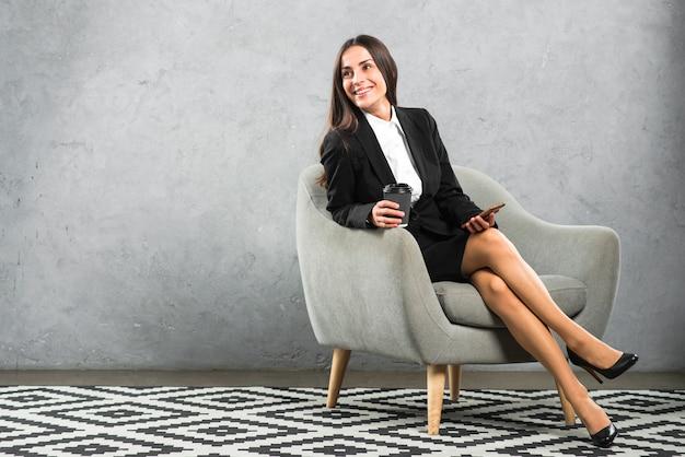 Giovane donna di affari sorridente che si siede sulla poltrona che tiene la tazza di caffè e sul cellulare eliminabili Foto Gratuite