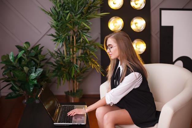 Giovane donna di bellezza in ubicazione di vetro nell'ufficio con il computer portatile. Foto Premium