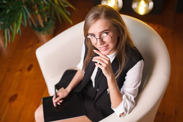 Giovane donna di bellezza in ubicazione di vetro nell'ufficio con la compressa Foto Premium