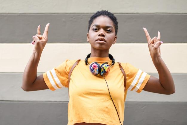 Giovane donna di colore che fa il gesto delle corna con le sue mani all'aperto. Foto Premium