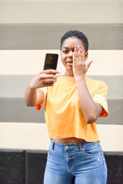 Giovane donna di colore che prende le fotografie del selfie con l'espressione divertente all'aperto Foto Premium