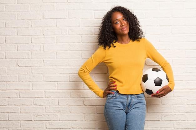 Giovane donna di colore con le mani sui fianchi, in piedi, rilassato e sorridente, molto positivo e allegro Foto Premium
