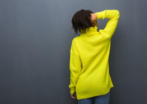 Giovane donna di colore da dietro a pensare a qualcosa Foto Premium