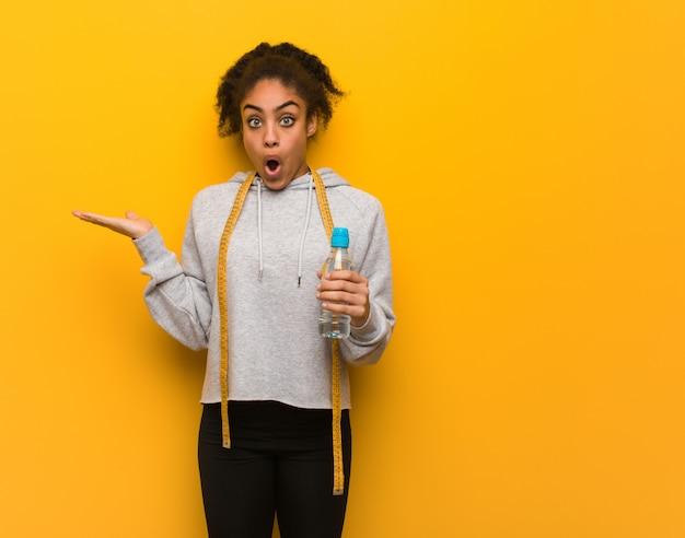 Giovane donna di colore di forma fisica che tiene qualcosa sulla mano della palma. holding una bottiglia di acqua. Foto Premium