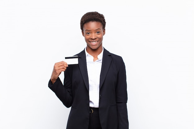 Giovane donna di colore piuttosto nera felice e piacevolmente sorpresa, eccitata con un'espressione affascinata e scioccata in possesso di una carta di credito Foto Premium
