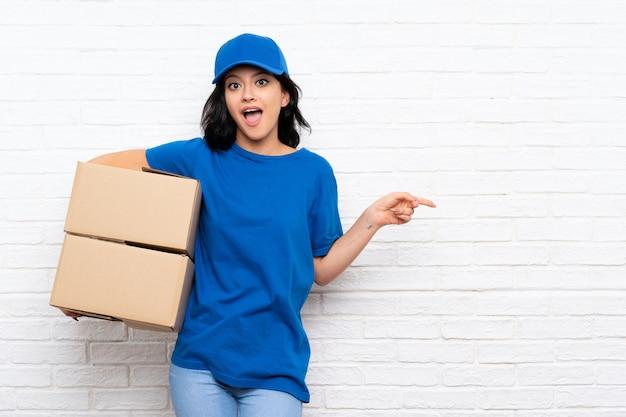 Giovane donna di consegna sul muro di mattoni bianchi sorpreso e puntando il dito verso il lato Foto Premium