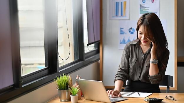Giovane donna di finanza che rivolge al telefono e che per mezzo del computer portatile. Foto Premium
