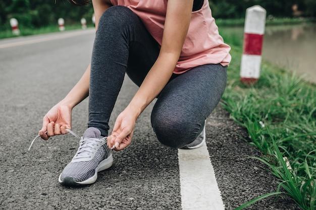Giovane donna di forma fisica che lega le scarpe da corsa in parco pubblico, concetto sano di stile di vita. Foto Premium