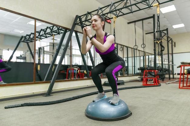 Giovane donna di forma fisica che si esercita nella palestra moderna di sport Foto Premium