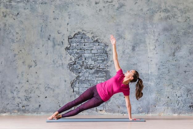 Giovane donna di forma fisica sportiva che fa pratica di yoga Foto Gratuite